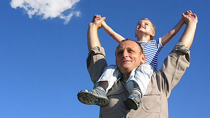Dad with son on shoulders with blue skies